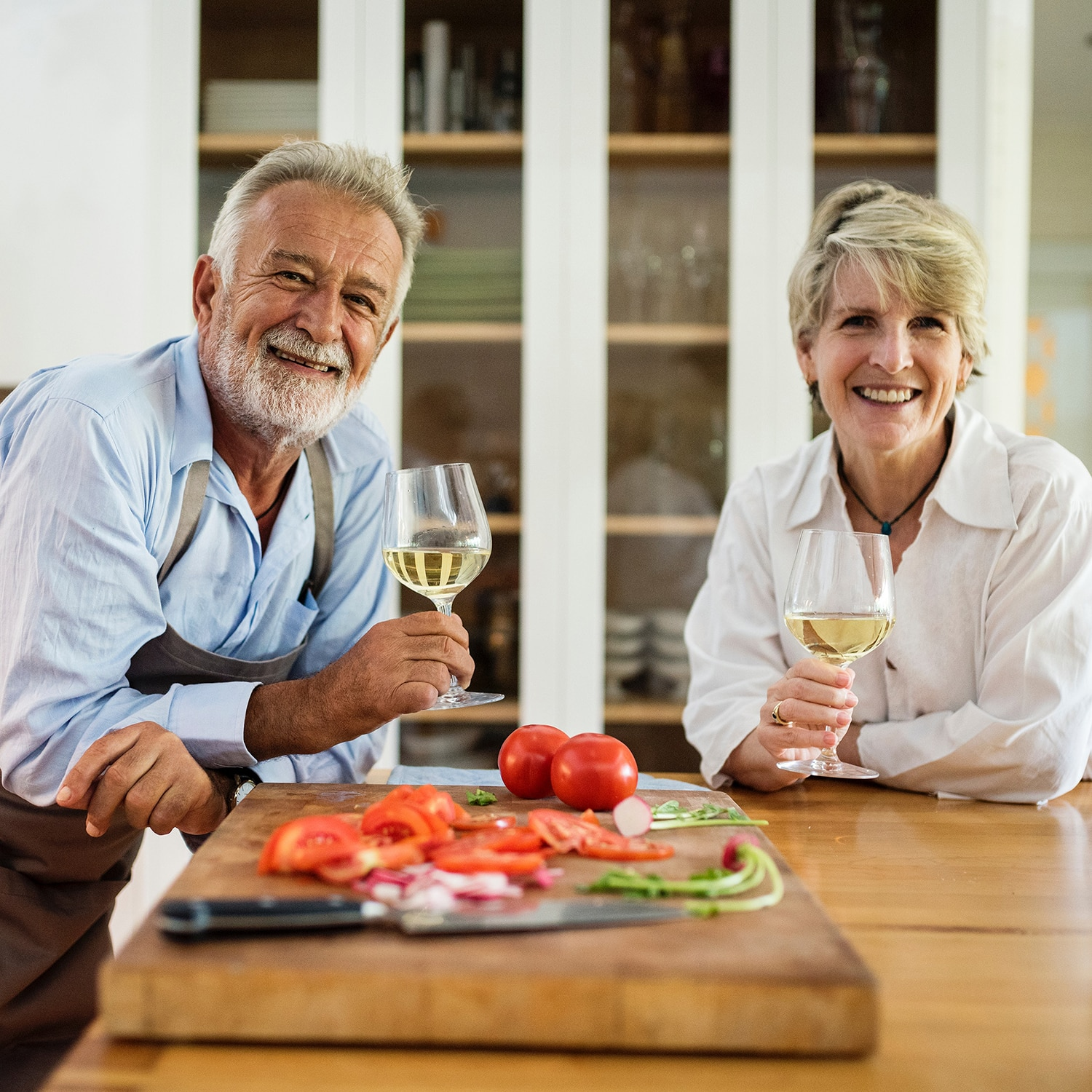 A couple of 62 year olds drinking wine after getting a reverse mortgage