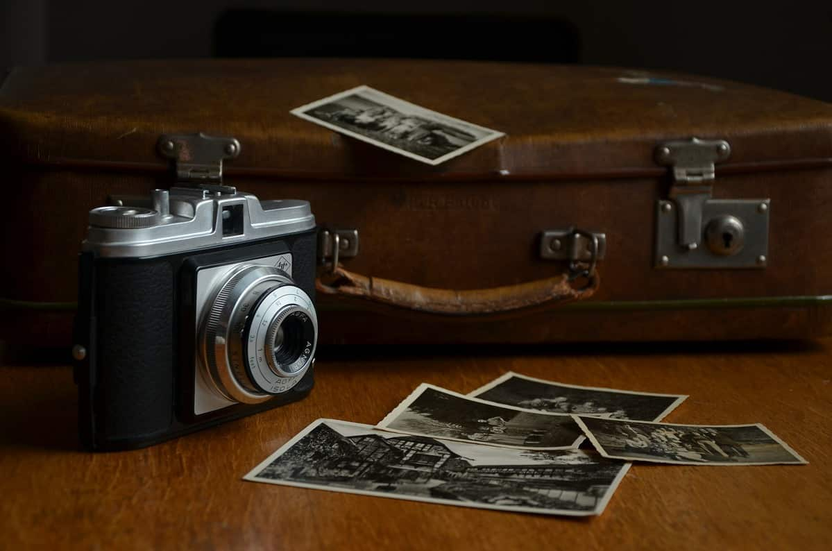 Vintage suitcase in the background; polaroid camera in the front left corner.