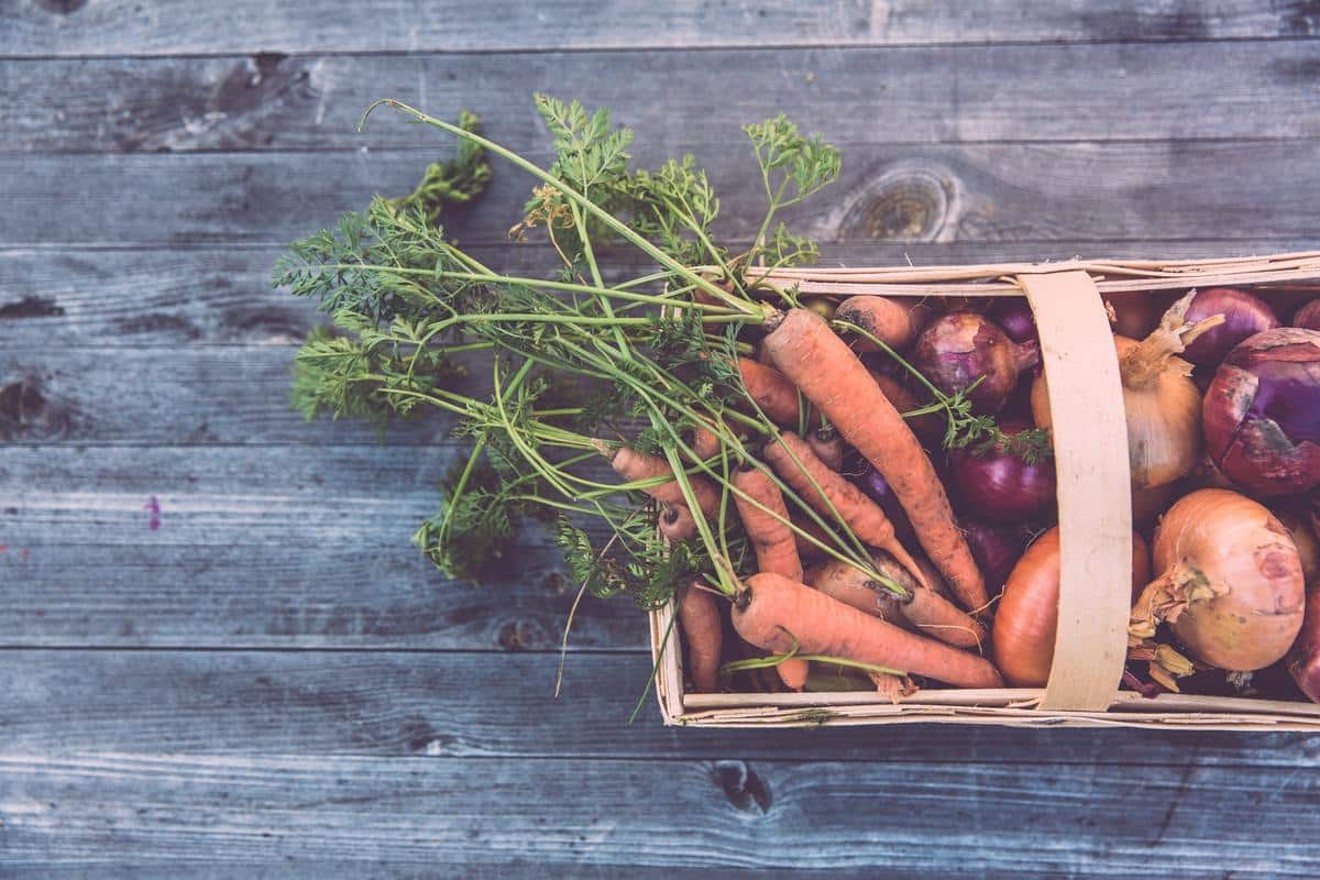 A basket of vegetables on a wooden surface.