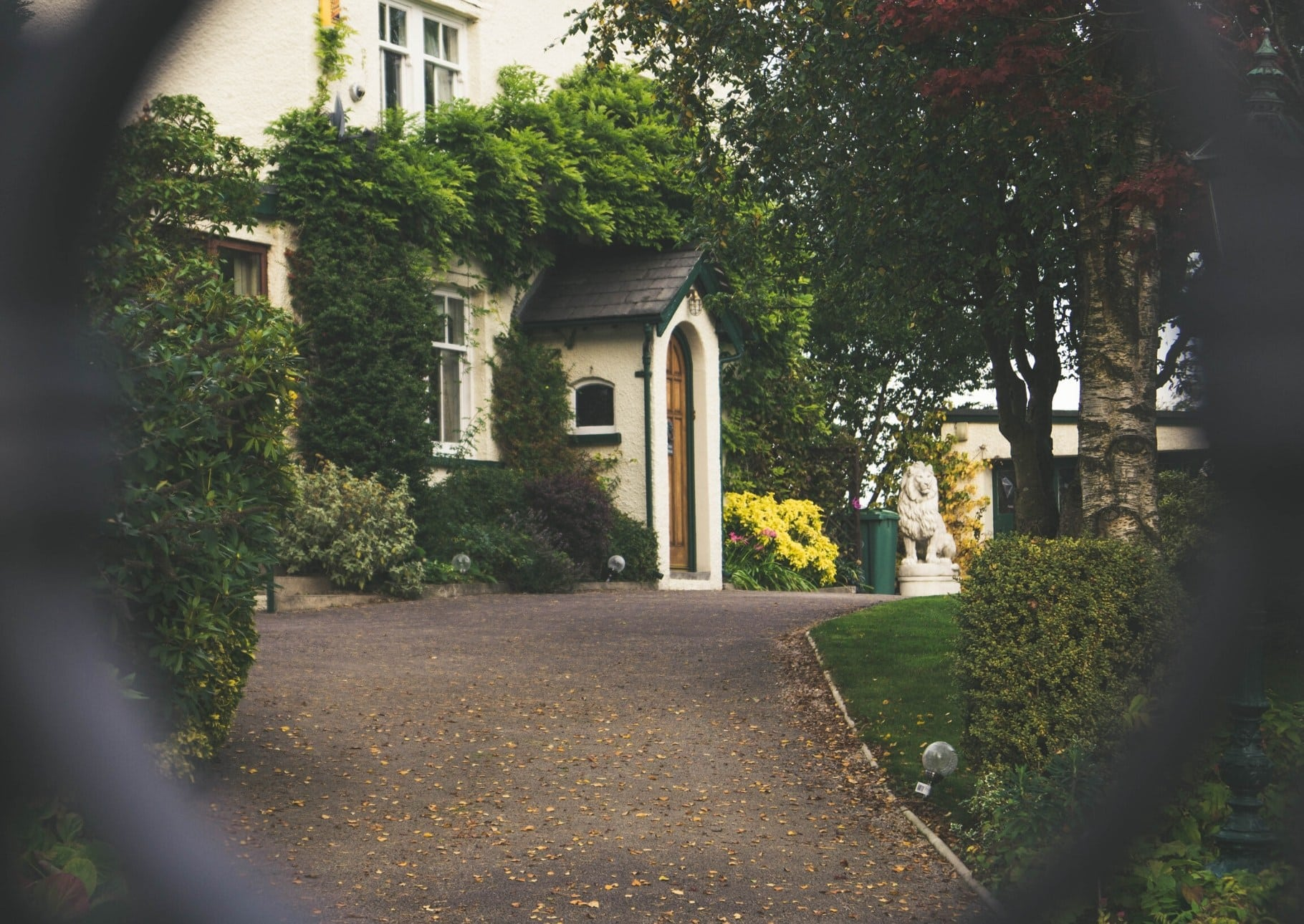 Shot of the front door and courtyard of a white house through a gate.
