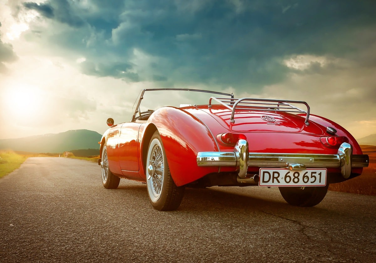 A red classic convertible faces down the open road.