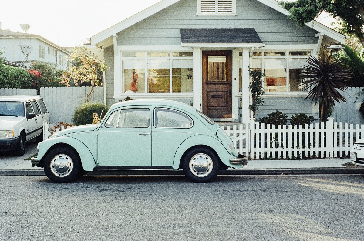 A VW Beetle in front of a single-story home with a white fence.
