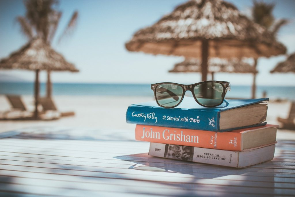 A stack of books with a pair of sunglasses on top with a background of a beach.