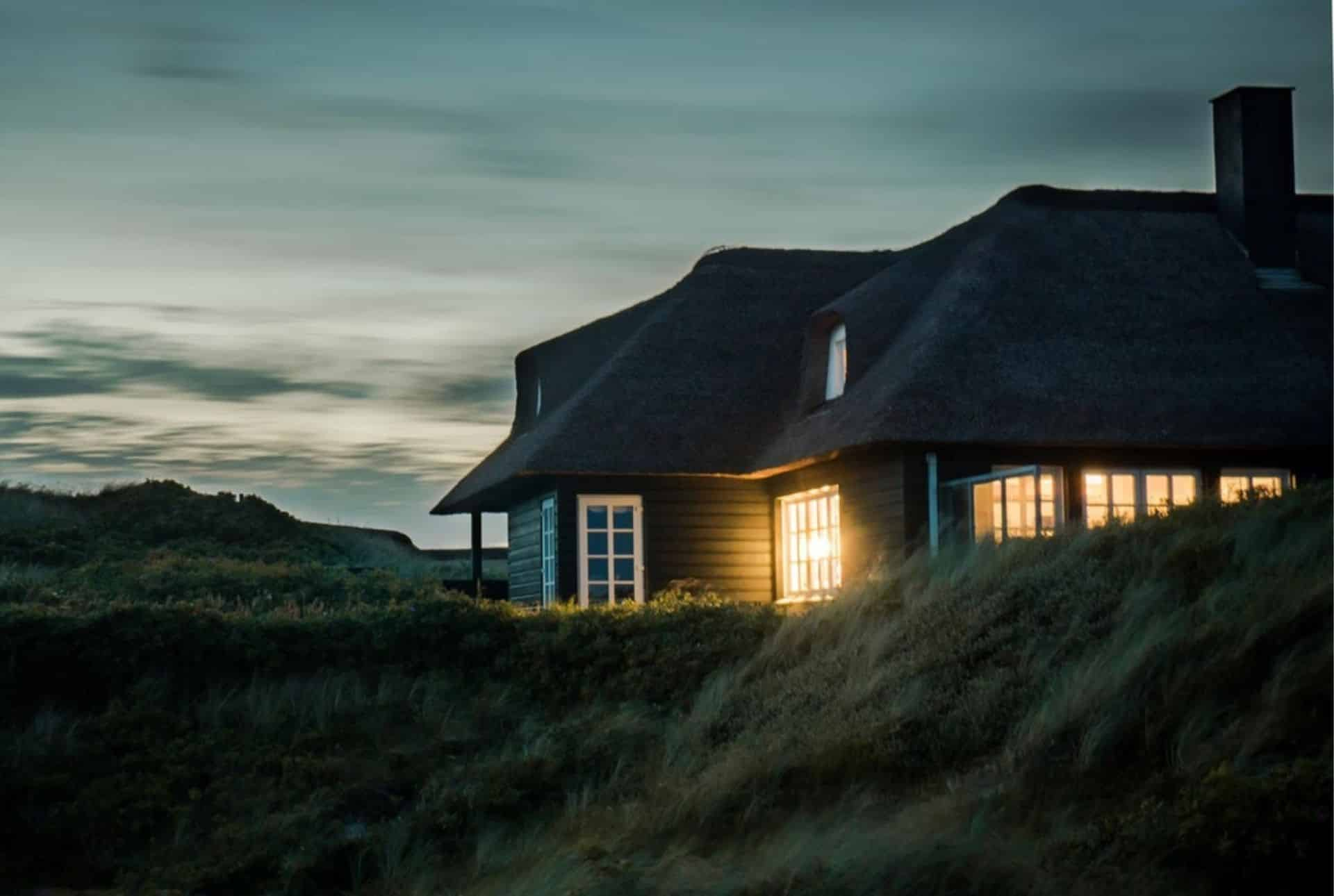 Gray house surrounded by grass under a blue, cloudy night sky.