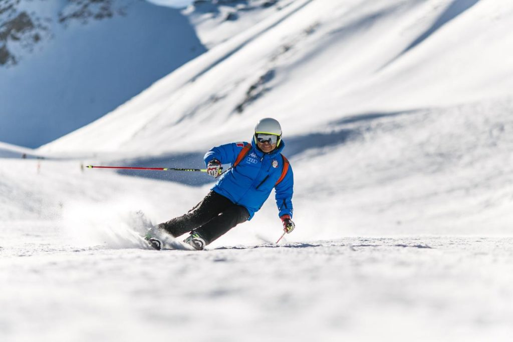 Man in blue coat snow skiing