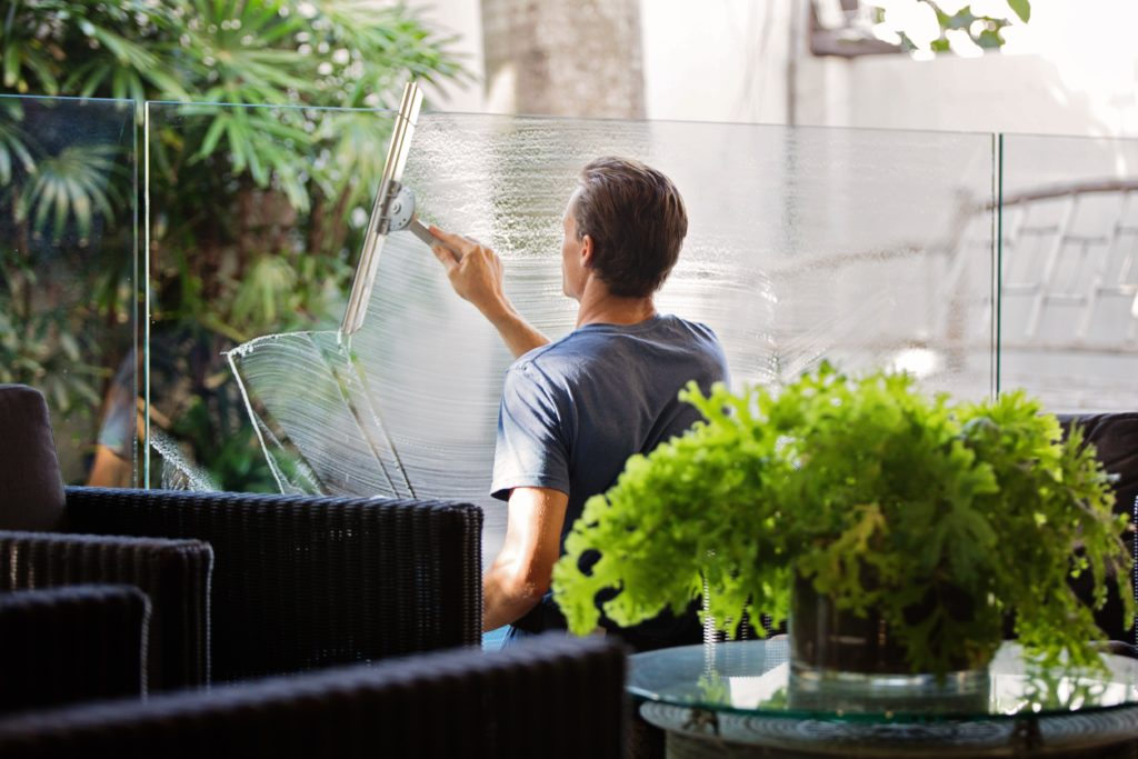 A man cleaning a glass fence in his backyard.