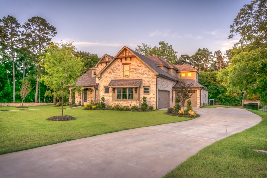 Brick home with a paved driveway and green lawn